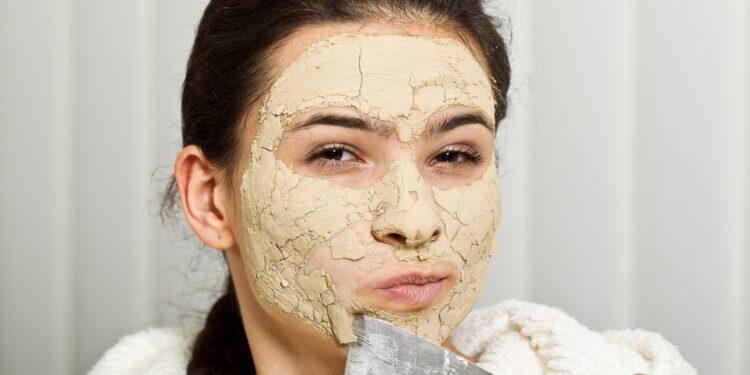 Eine Frau in weißem Bademantel kratzt sich mit einem Spachtel die Reste einer Kieselerde-Gesichtsmaske ab.