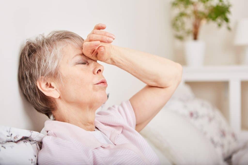 Seniorin mit Kopfschmerzen im Bett