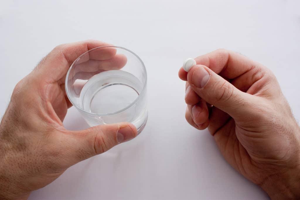 Eine Hand hält ein Wasserglas, die andere eine Tablette