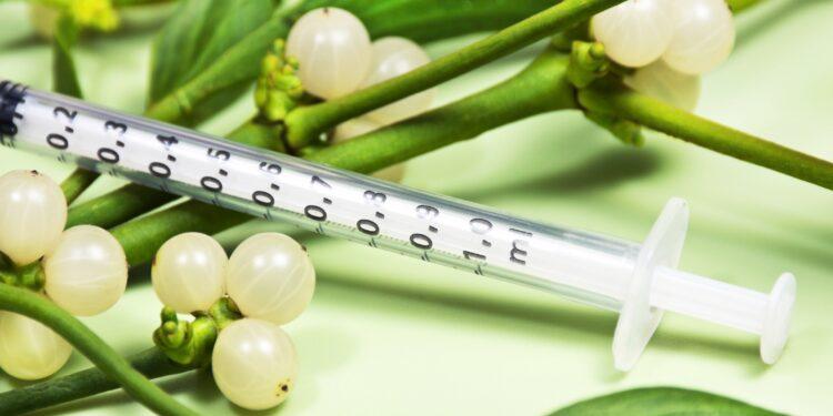 Spritze mit Maßeinheiten liegt auf einem grünen Mistelzweig mit weißen Beeren