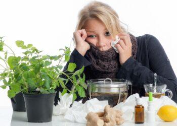Erkältete Frau mit Taschentuch sitzt zwischen vielen verschiedenen naturheilkundlichen Mitteln