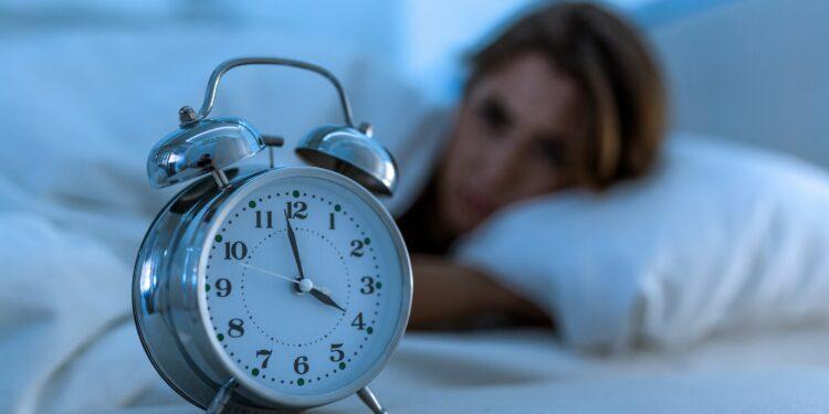 Wecker auf 4 Uhr im Vordergrund, schlaflose Frau im Hintergrund