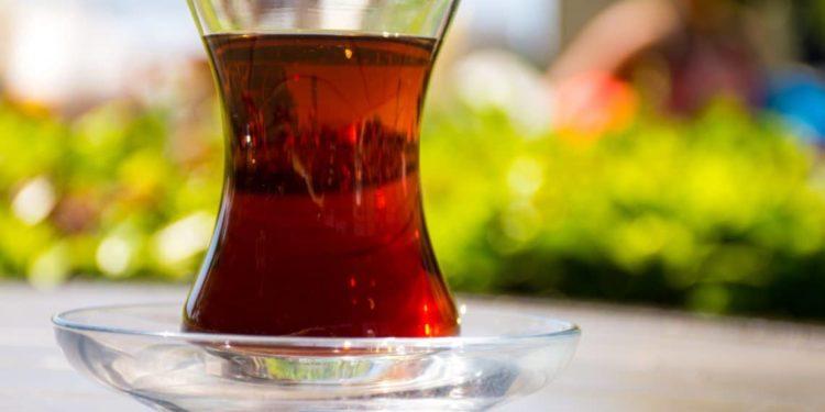 Kleines Teeglas gefüllt mit schwarzem Tee.