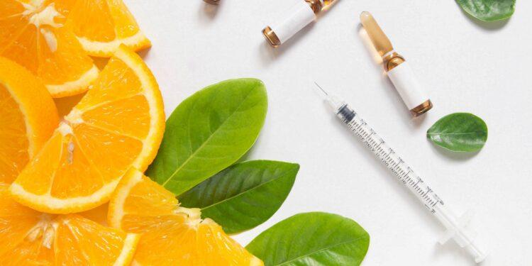 Orangenscheiben und -blätter mit Ampullen und einer Spritze