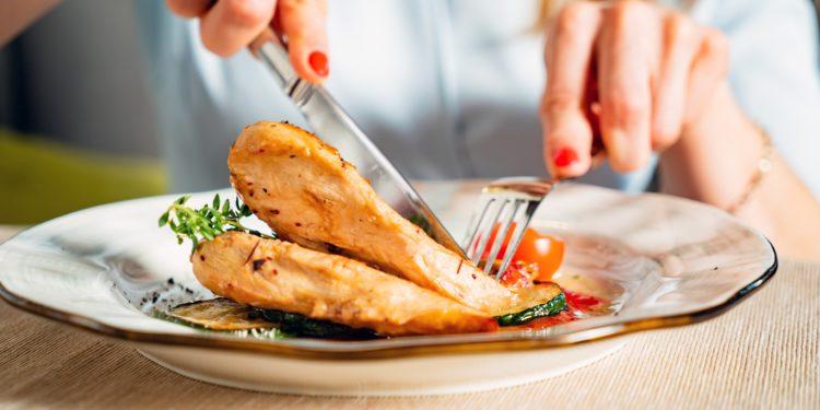 Eine Frau isst gegrillte Hähnchenbrust