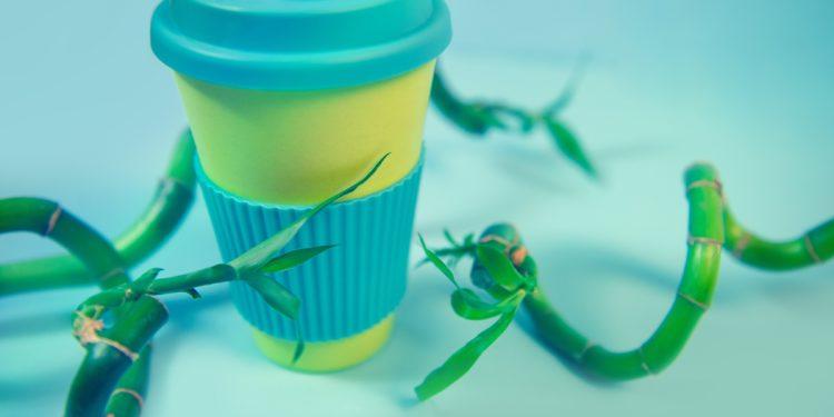 Ein Coffee-to-go-Becher steht zwischen Bambus-Halmen.