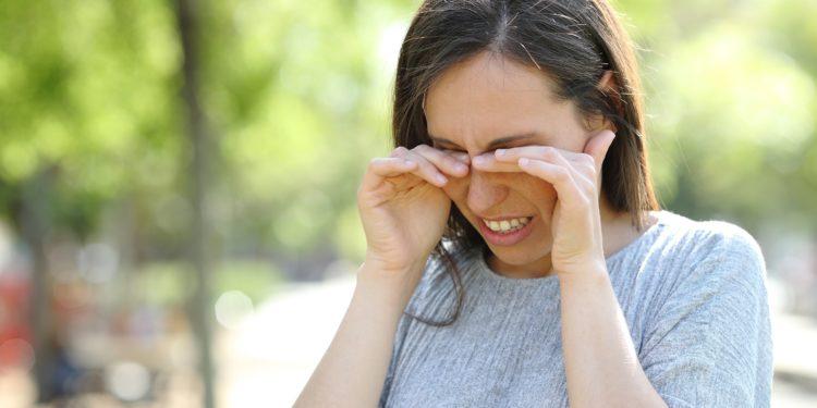 Eine Frau steht in einem Park und reibt sich die Augen.