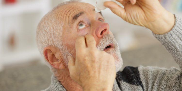 Ein älterer Mann tropft sich Augentropfen ins Auge.