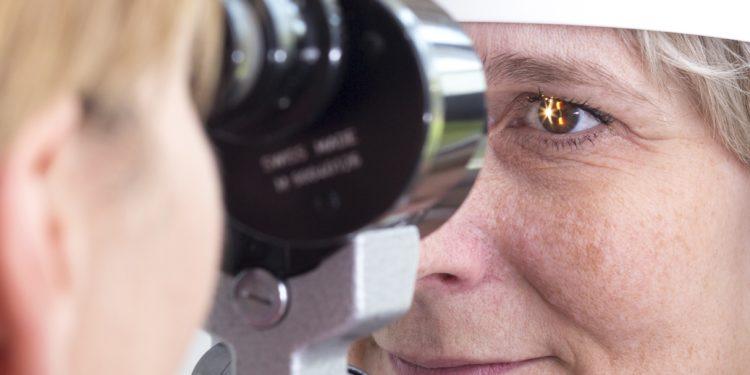 Eine Augenärztin untersucht die Augen einer Frau mithilfe der Spaltlampe.