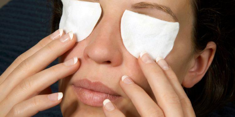 Eine Frau hat Wattepads als Kompressen auf den Augen und hält diese mit den Fingern fest.