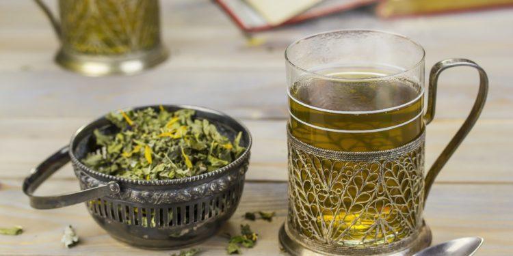 Ein Glas mit Tee neben einem Schälchen mit Teekräutern.