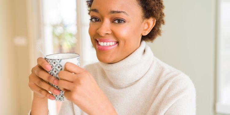 Eine lächelnde Frau hält eine Tasse Tee in den Händen.