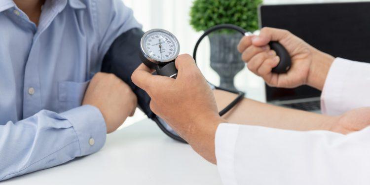 Arzt misst bei einem Patienten den Blutdruck