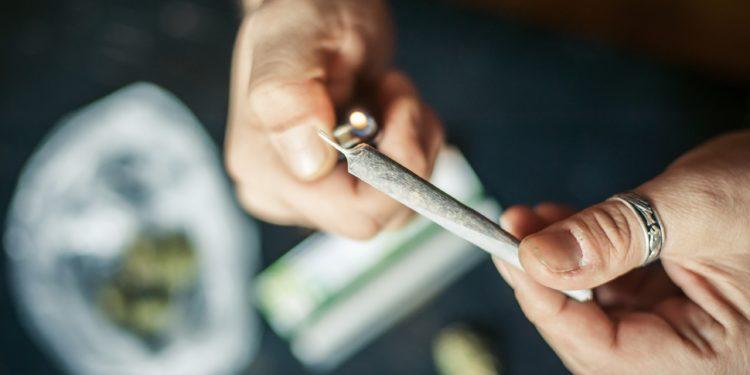 Eine Hand mit einem Feuerzeug zündet einen Joint an