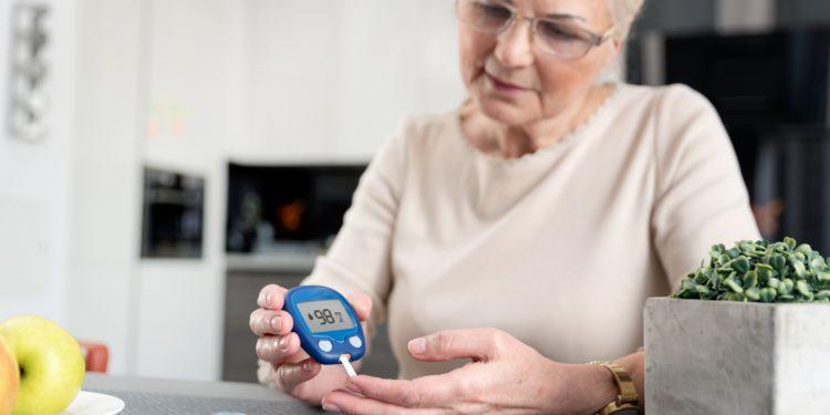 Ältere Frau prüft zu Hause ihren Blutzuckerspiegel