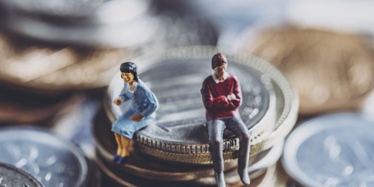 Miniatur Mann und Frau sitzen auf Münzen.