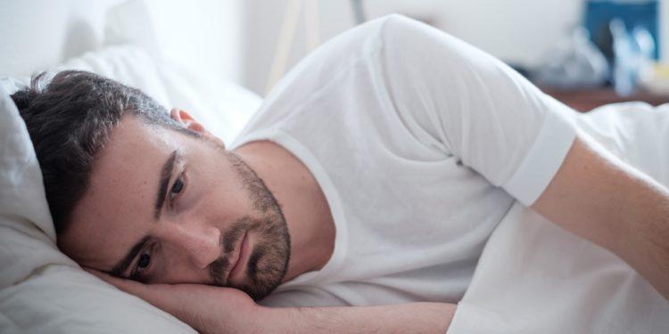 Ein traurig blickender Mann liegt zugedeckt im Bett.