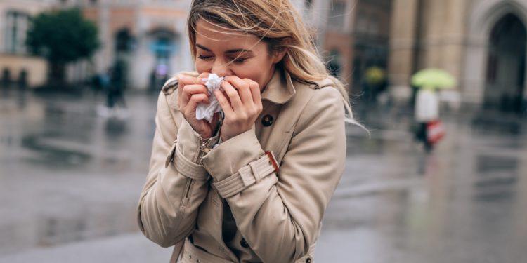Frau putzt sich bei nasskaltem Wetter die Nase