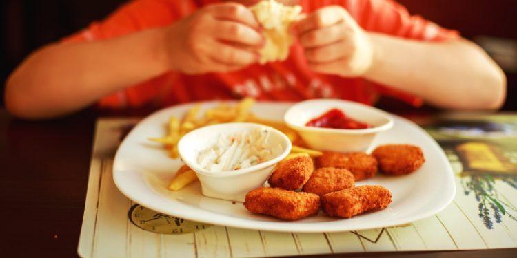 Kind sitzt vor einem Teller mit Fast Food.