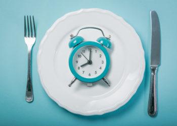 Besteck neben einem Teller auf dem ein Wecker liegt