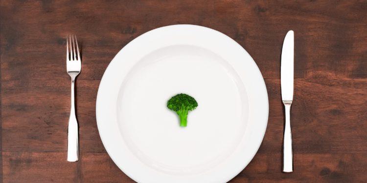 Teller mit einem Brokkoliröschen darauf und Besteck daneben