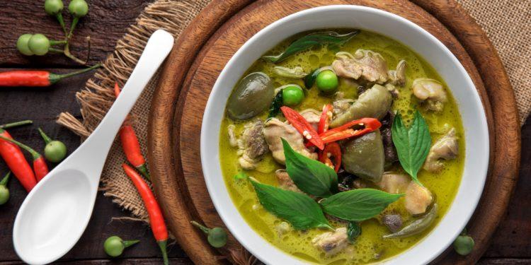 Eine Schale mit grünem Thai-Curry auf einem Holzbrett und ein Löffel.