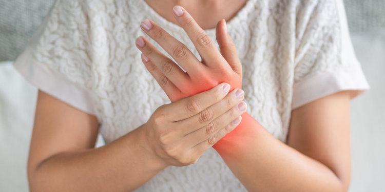 Frau hält sich das schmerzende Handgelenk.