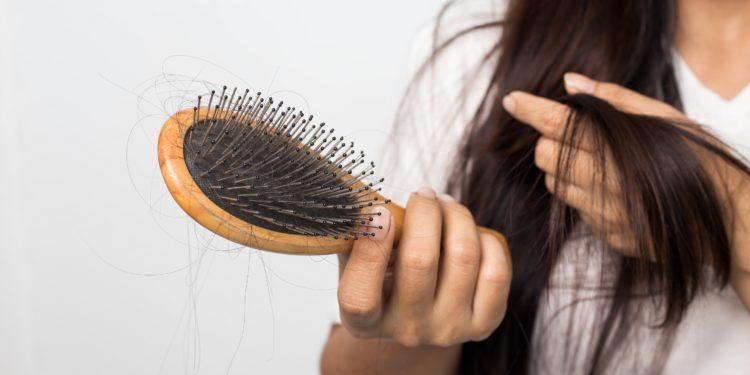 Junge Frau mit einer Haarbürste voller ausgefallener Haare