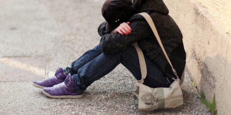 Junges Mädchen sitzt auf dem Boden und hat ihren Kopf in ihre verschränkten Arme gelegt