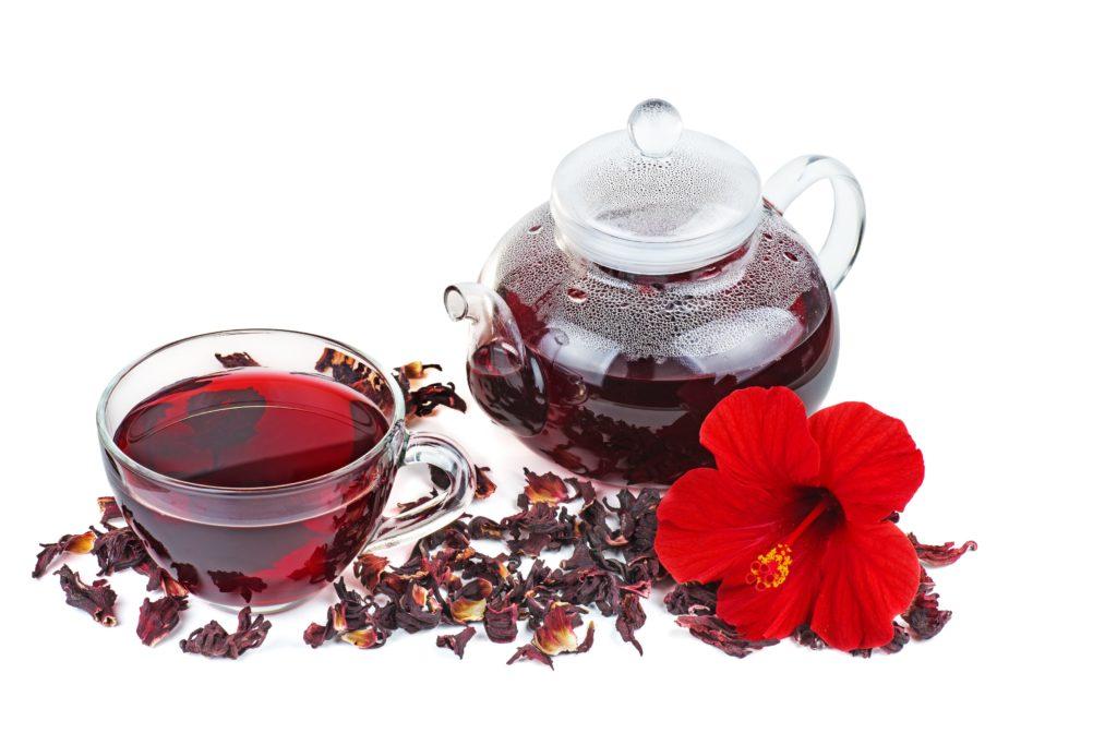 Eine Teekanne und Teetasse mit rotem Hibiskustee, drumherum getrocknete Hibiskusblüten und eine große frische Blüte.