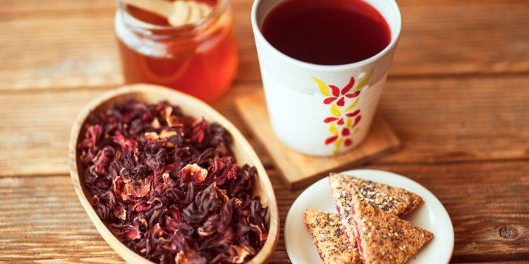 Auf einem Holztisch stehen ein Becher mit Hibiskustee, ein Glas mit Honig, eine Schale mit Hibiskusblüten und ein kleiner Teller mit Gebäck.