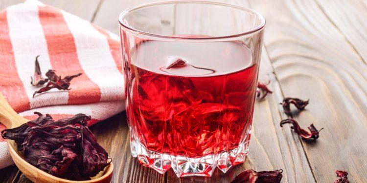 Auf einem Holztisch steht ein Glas Hibiskustee mit Eiswürfeln, daneben liegt ein rot-weiß kariertes, zusammengefaltetes Geschirrhandtuch und ein Holzlöffel mit getrockneten Hibiskusblüten.