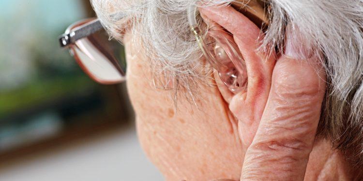 Alte Frau mit Brille und Hörgerät