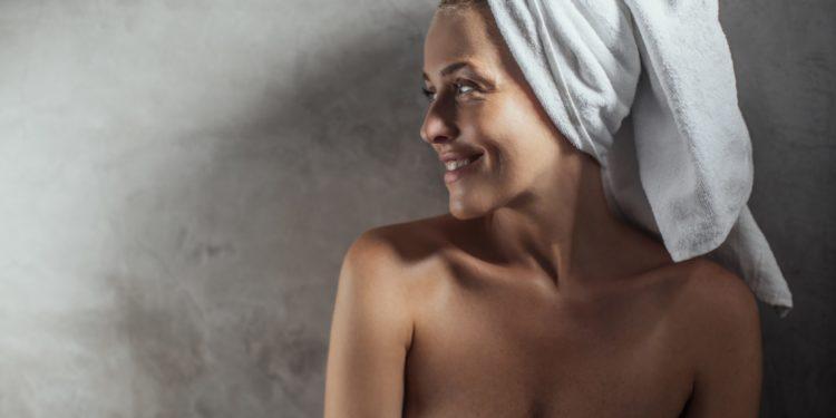 Eine Frau mit einem Handtuch-Turban und einem um den Oberkörper gewickelten Handtuch lächelt entspannt.