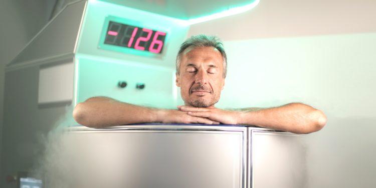 Ein Mann sitzt in einer Kältesauna, die auf einem Display eine Temperatur von minus 126 Grad Celsius anzeigt.