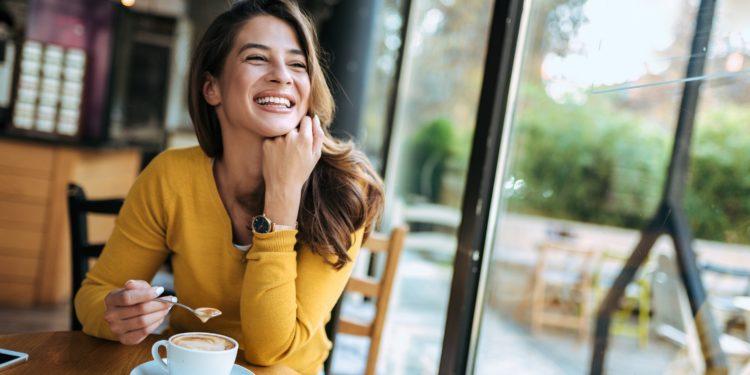 Eine Frau mit glücklichem Gesichtsausdruck sitzt an einem Fenster und trinkt Kaffee.
