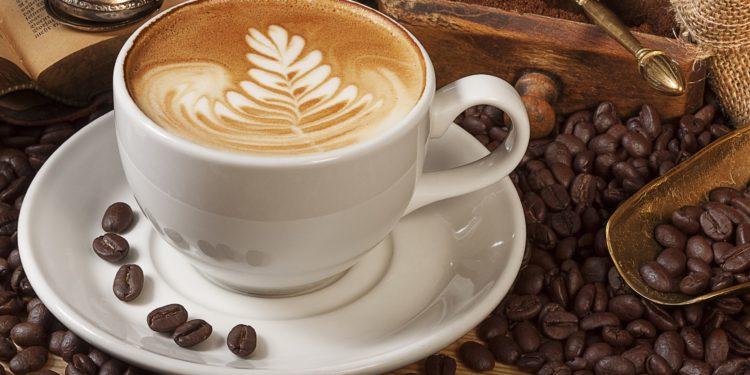 Eine Tasse Kaffee steht auf einem Tisch und ist von Kaffeebohnen umgeben.