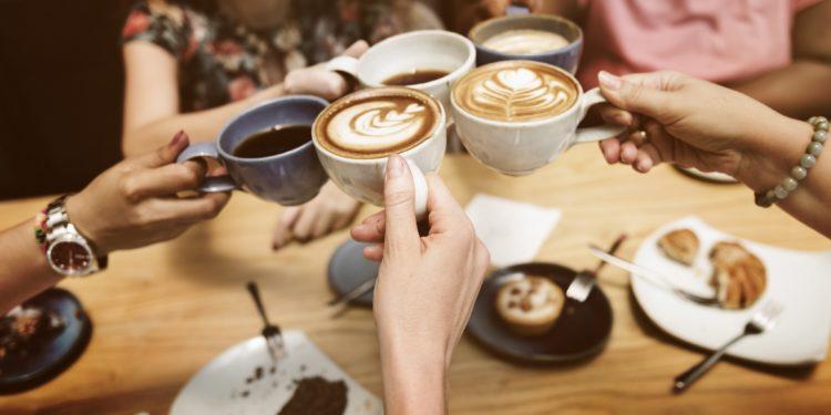 Vier Hände halten jeweils eine Kaffeetasse und stoßen damit an