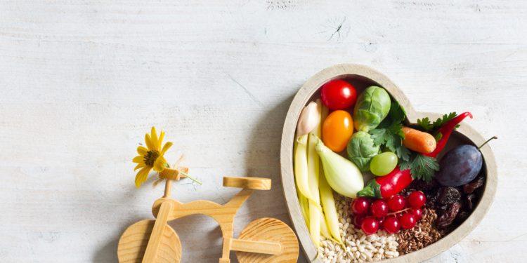 Herzfömige Schale gefüllt mit Obst und Gemüse. Links daneben ein Spielzeug Holzfahrrad.