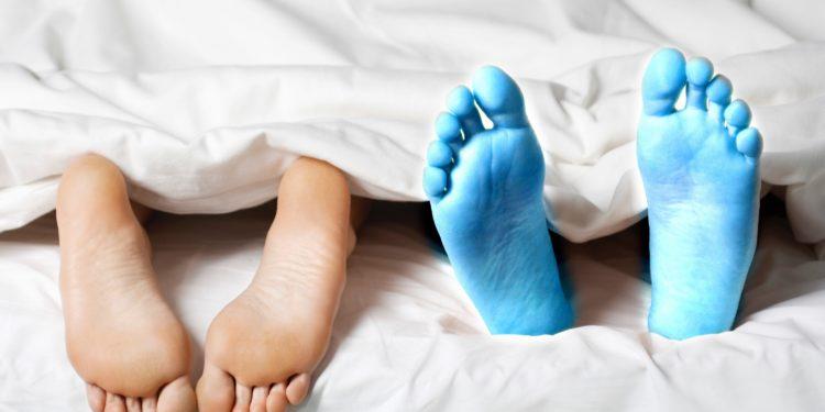 Zwei paar Füße gucken unter der Decke hervor, eines davon blau gefroren.