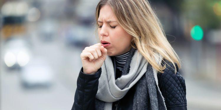 Eine Frau steht auf der Straße, hustet und hält sich dabei die Hand vor den Mund.