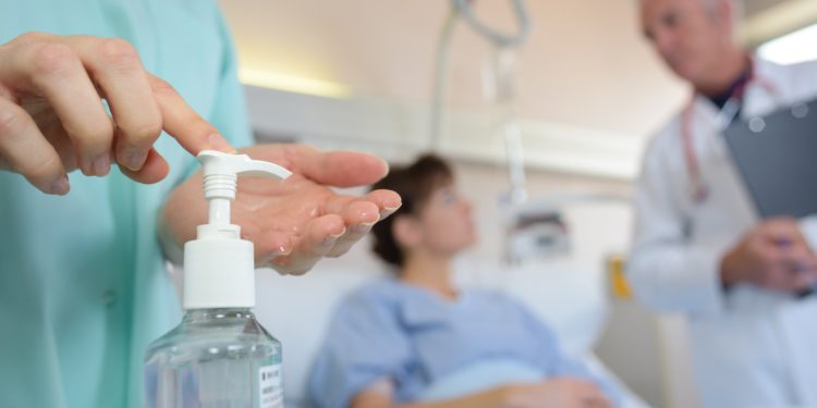 Ein Arzt desinfiziert seine Hand mit Desinfektionsmittel.