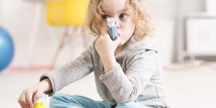 Ein junges Mädchen benutzt einen Asthma-Inhalator.