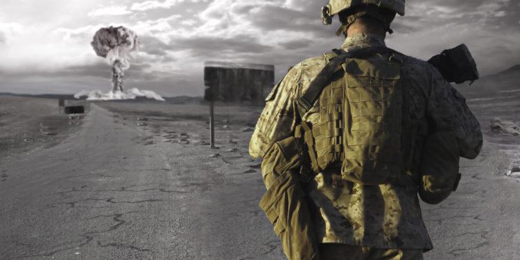 Ein Soldat betrachtet eine Explosion am Horizont.