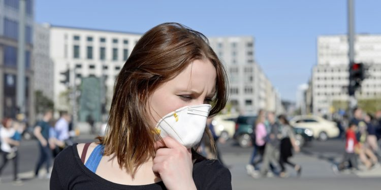 Frau in einer Stadt trägt einen Mundschutz