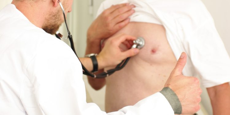 Ein Arzt horcht mit einem Stethoskop die Lunge eines Mannes ab.