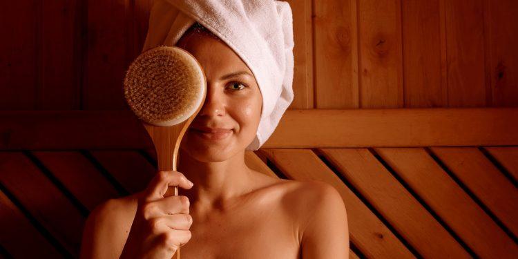 Frau mit weißem Handtuchturban sitzt in der Sauna und hält sich eine Massagebürste vor das rechte Auge.