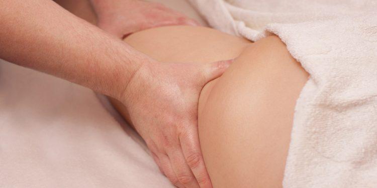 Hände massieren geschwollene Extremität mit Griffen der Lymphdrainage.