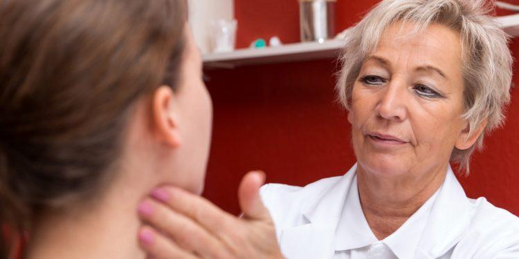 Ärztin tastet die Lymphknoten am Hals einer jungen Frau ab.