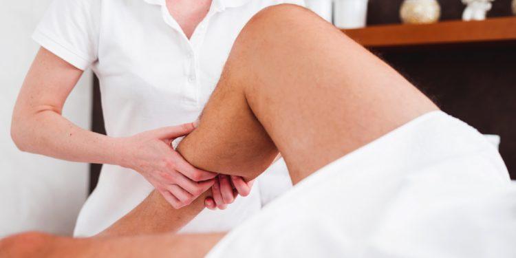 Eine Therapeutin führt eine Lymphdrainage am Unterschenkel eines Mannes durch.